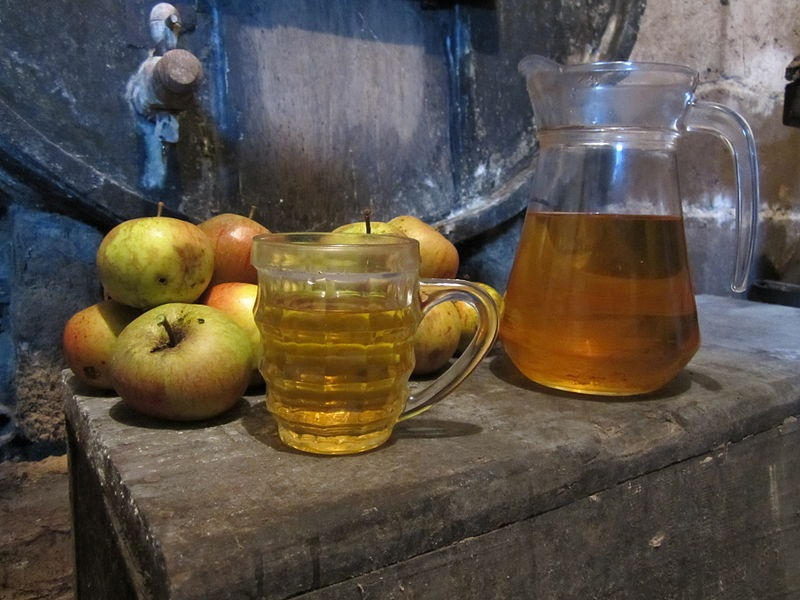 Apples, cider jug, glass and barrels from a Normandy cellar