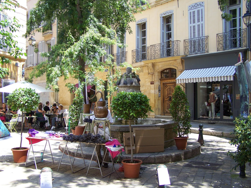 Shady square with fountain, ochr houses and cafes in Aix-en-Provence
