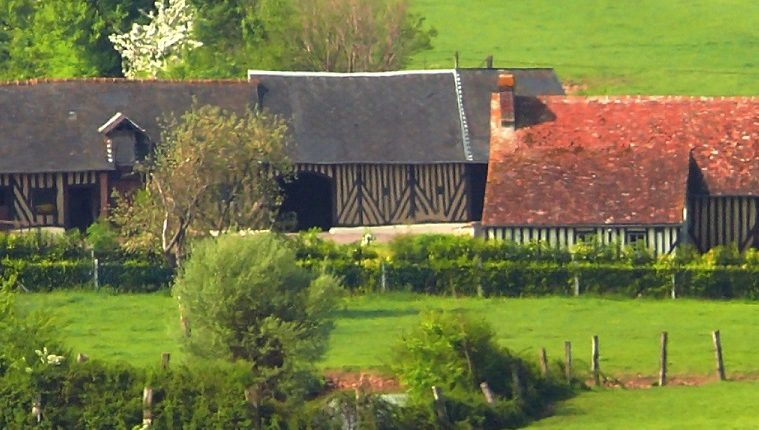Normandy countryside with half timbered barns, red rooved houses and green pastures