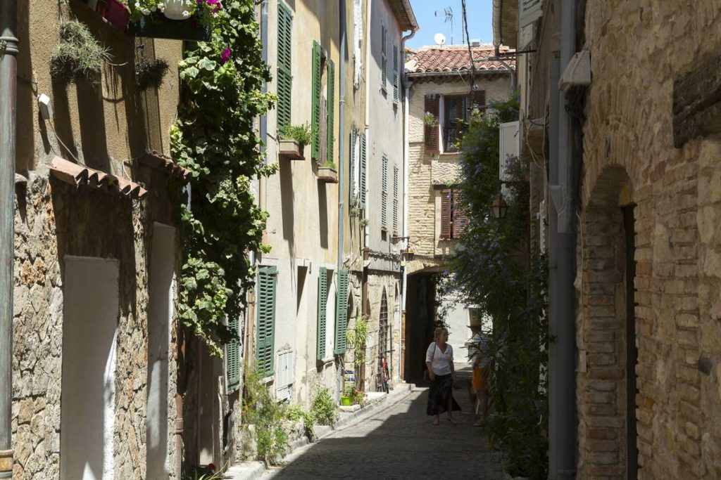 narrow cobbles little streets in antibes with stone houses and flowers