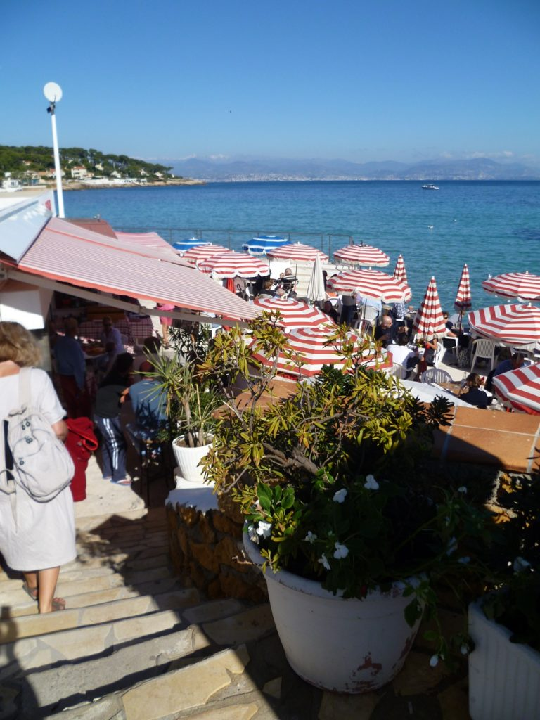 walking down steps to tables with parasols at La Garoupe beach