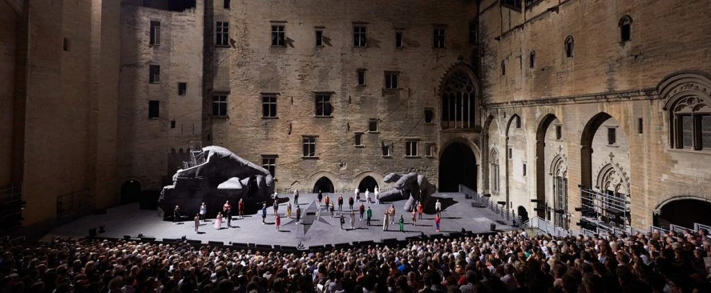 Dark stage with performers and papal palace b ackdrop avignon festival