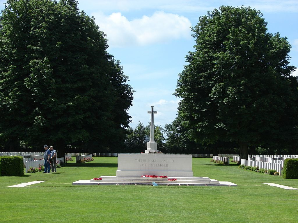 Bayeux war cemetery with cross on marble block and graves to each side