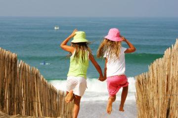 2 small girls run down a path to the sea
