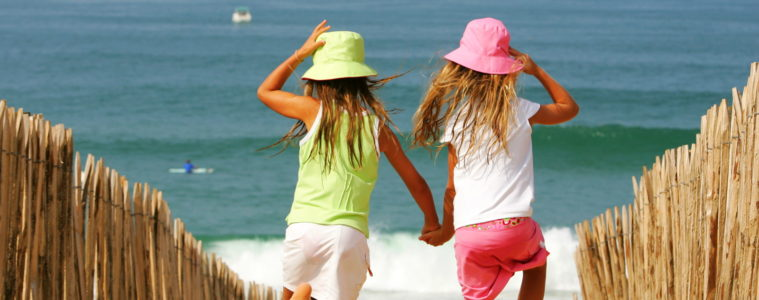 2 small girls run down a path to the sea