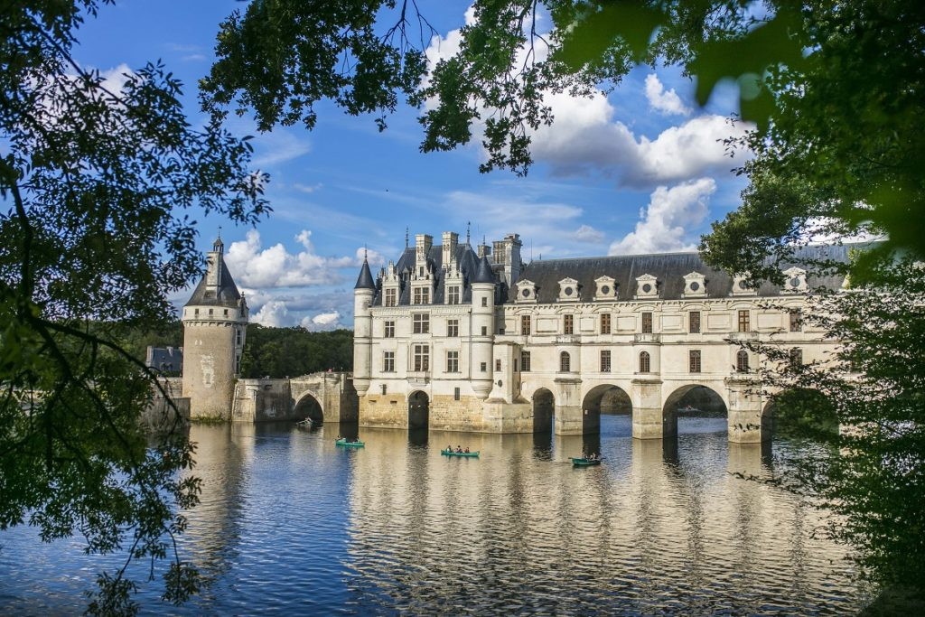 Chateau de Chenonceau built in the lake with its white walls and towers reflected in the water
