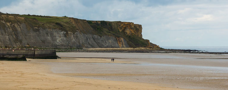 Gold beach, Arromanches with long stretch of golden sand and cliff in background