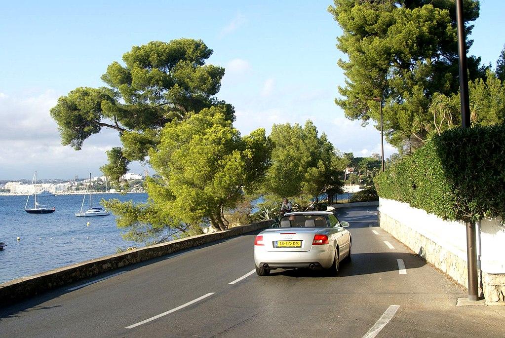 Open top car driving along road towards Juan les Pins