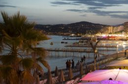 Juan les Pins at night with lit up bars in foreground and sea at back