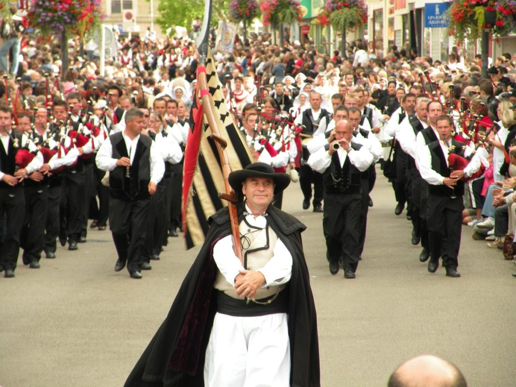 Procession of men with bagpipes in the street at Lorient Interceltic festival