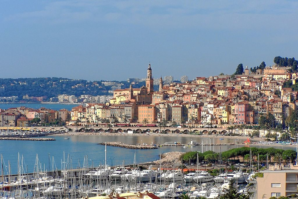 Menton on the hill with pastel coloured houses and towers and yachts in the water