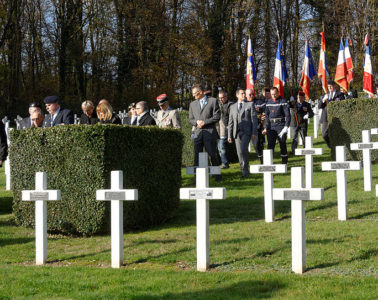 Armistice Day. Soldiers and citizens walk down path at cemetery