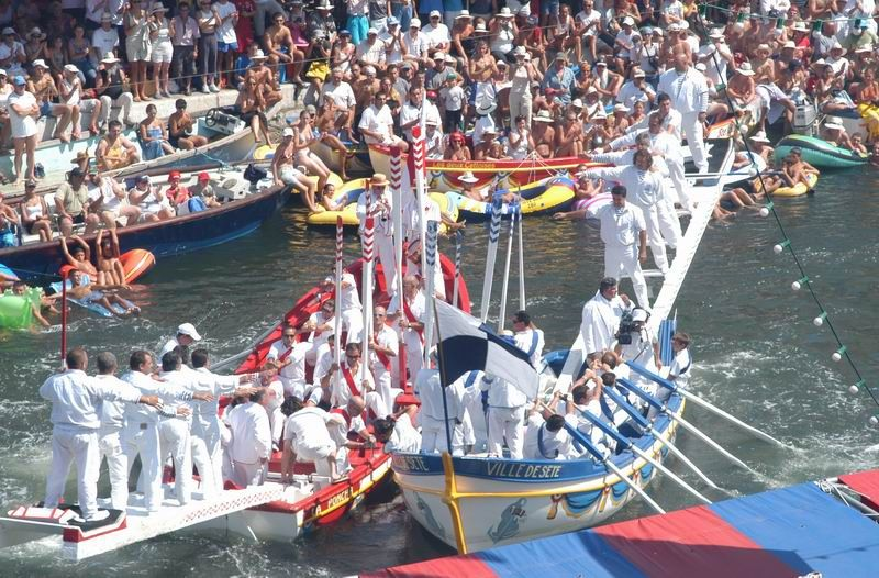 Boats full of rowers in fancy dress in the water at Sete