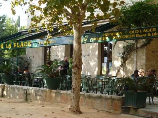 Shaded cafe in st paul de vence with terrace tables at autumn