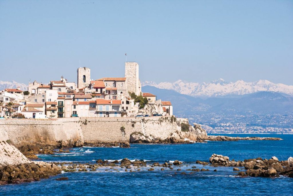Antibes ramparts and castle seen from afar with snow-covered Alps in background