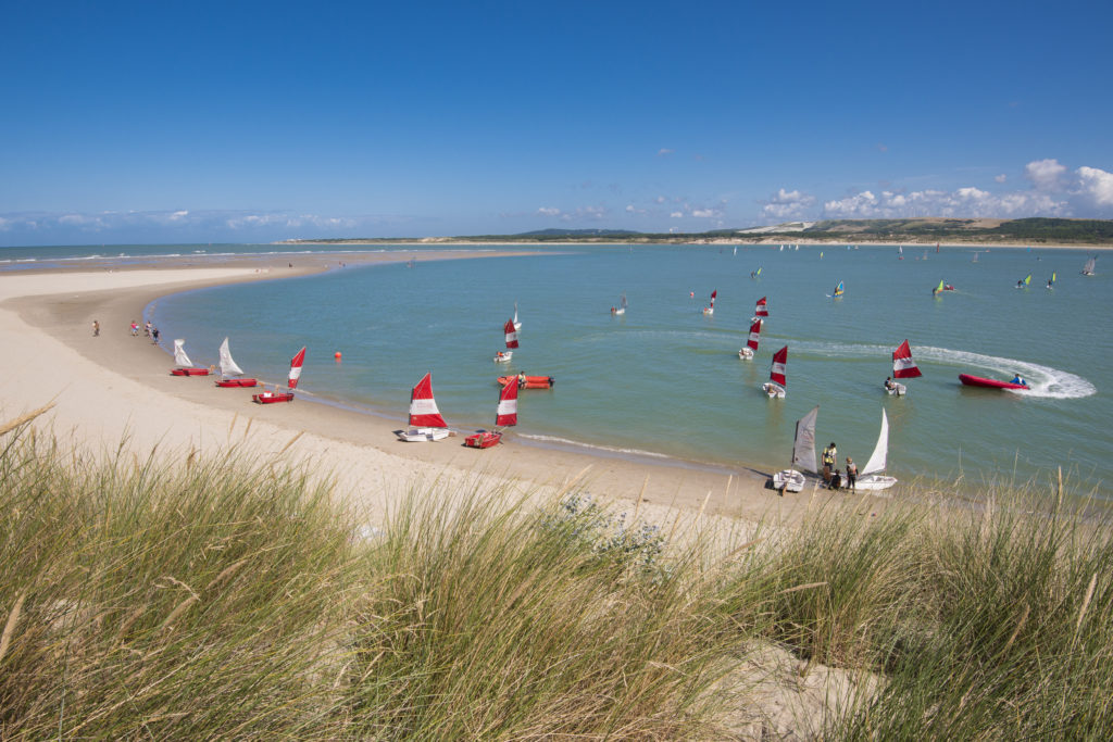 from sand dunes onto beach with many small sailing boats and children learning to sail at Le Touquet Paris-Plage