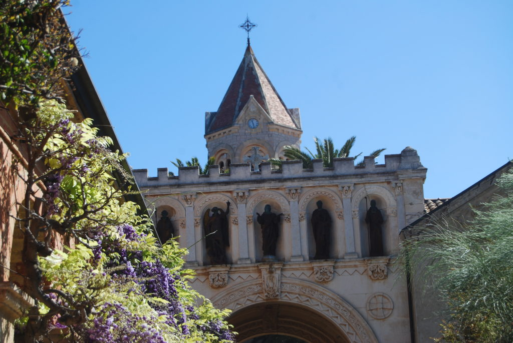 Monastery tower against blue sky with trees in foreground Ile St Honorat