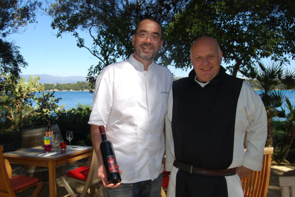 Monk and chef pose on  St Honorat with sea and tree in background
