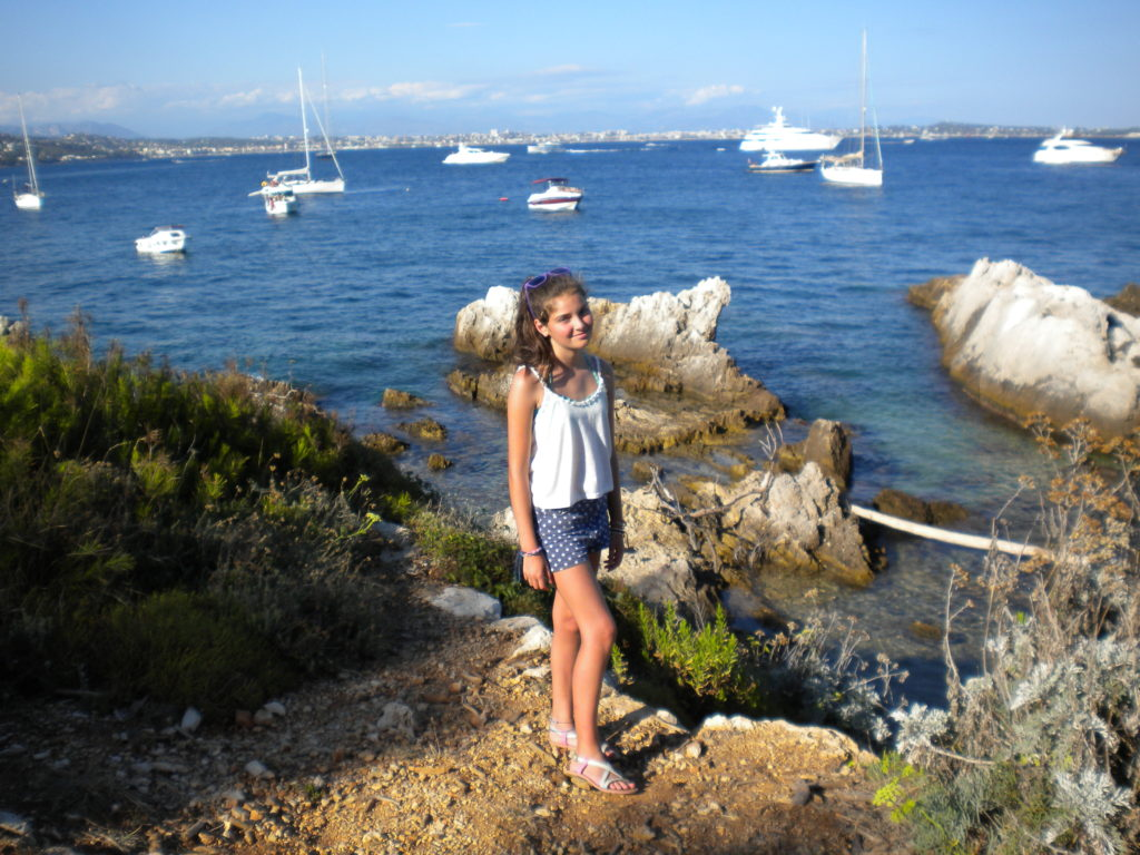 Young girl on headland at Ste Marguerite with sea and yachts in background