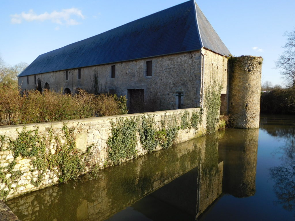 View over moat onto old wall and stone building of Chateau de Vouilly Normandy