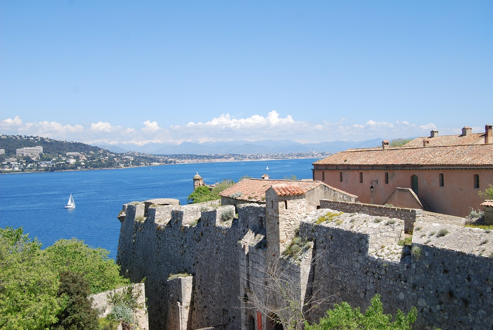 View of Fort Royal on Ste Marguerite with fortified walls and red tiled roofed buiildings and sea behind