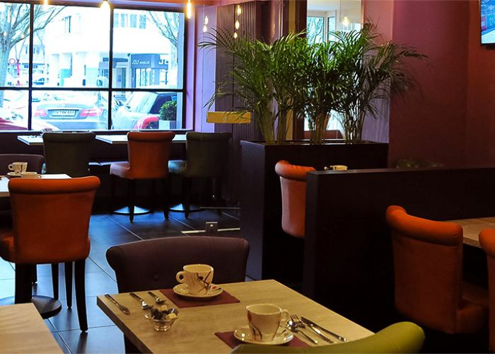 Tables and chairs in a breakfast room looking out onto street. Hotel des Quatrans Caen