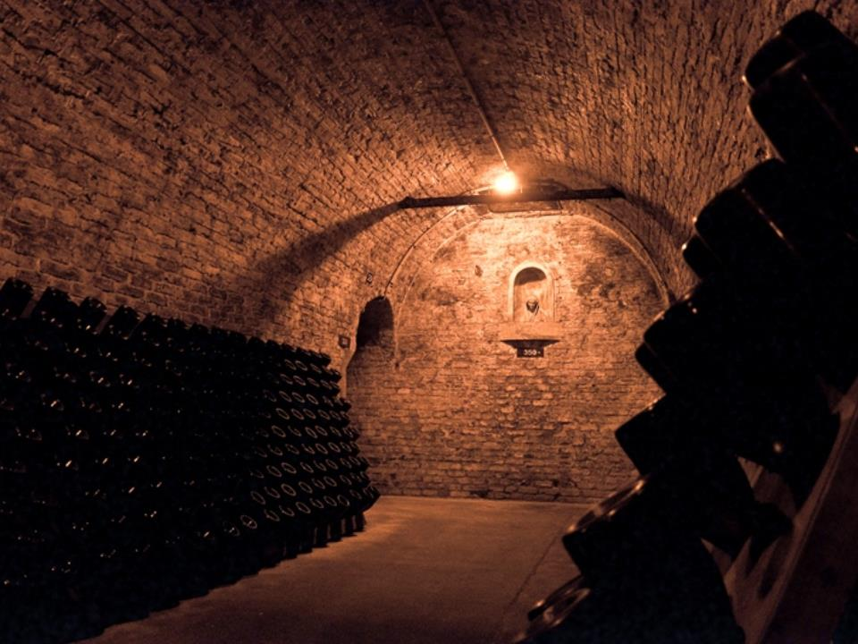 Vaulted cellars of Lanson Reims with dimly lit stone cave and racks of bottles