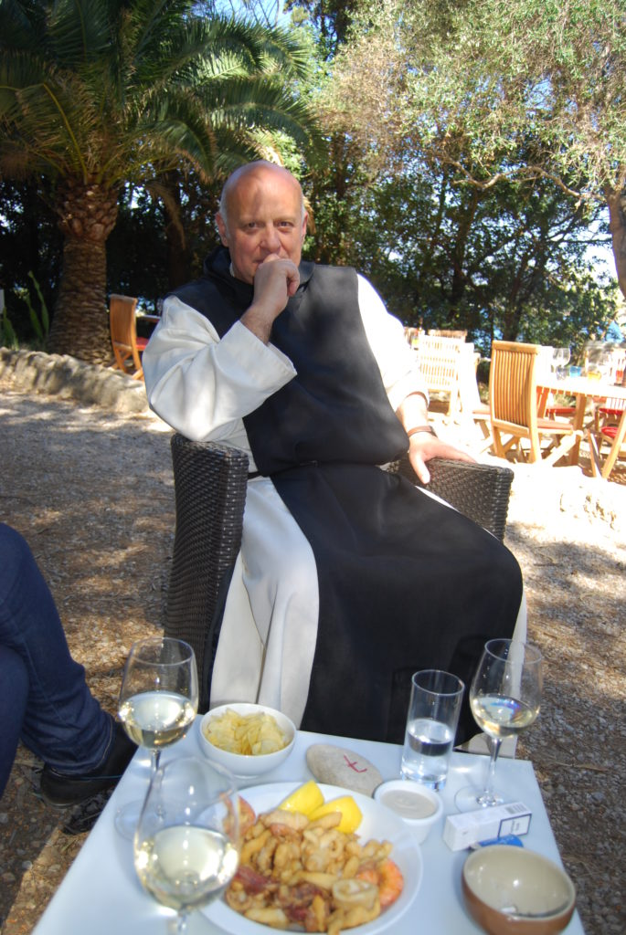Monk on chair in open air with table of food and wine in front of him on St Honorat