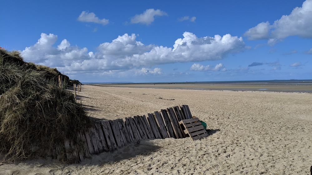 Utah Beach mainly sand with old wooden fence and view to sea and clouds