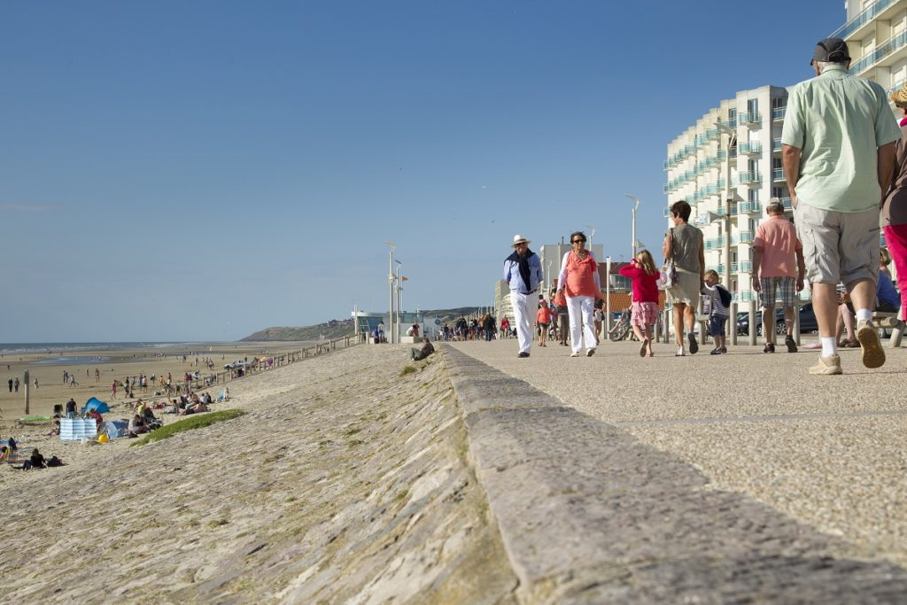 Sand to left, walkers along seafront in Hardelot and apartment blocks