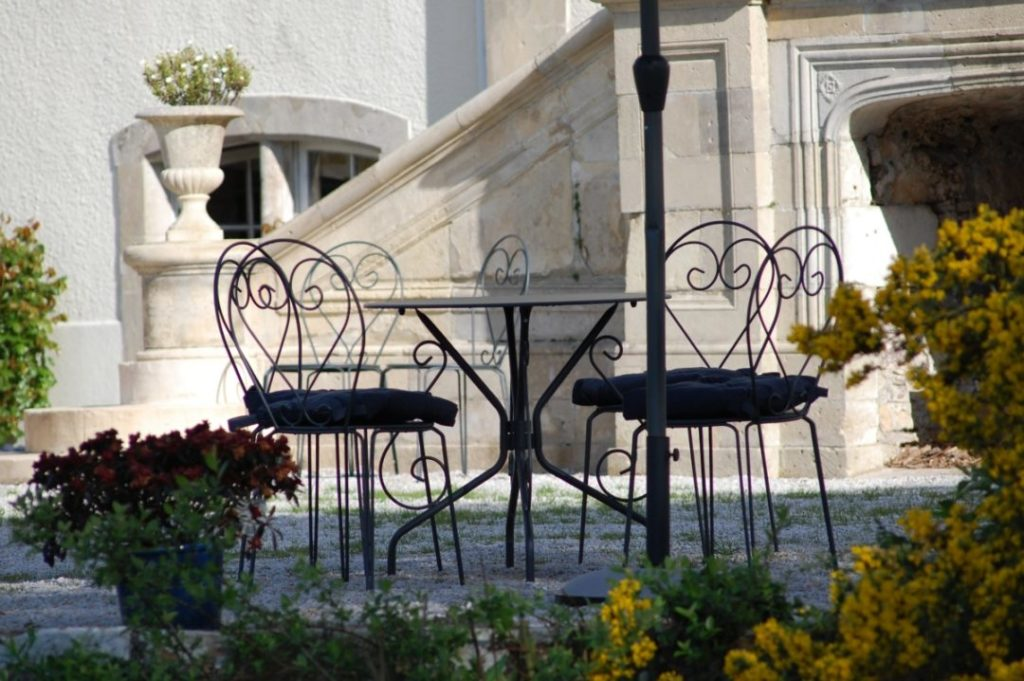 Chairs and stairs on a stone terrace at Chateau de Quineville