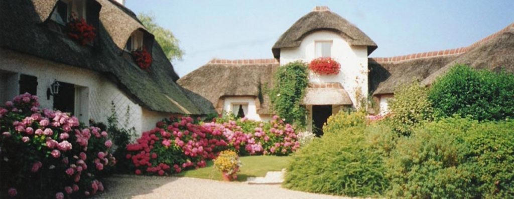 thatched cottages with white walls in leafy garden at La Chaumiere BnB in Berck sur Mer north France