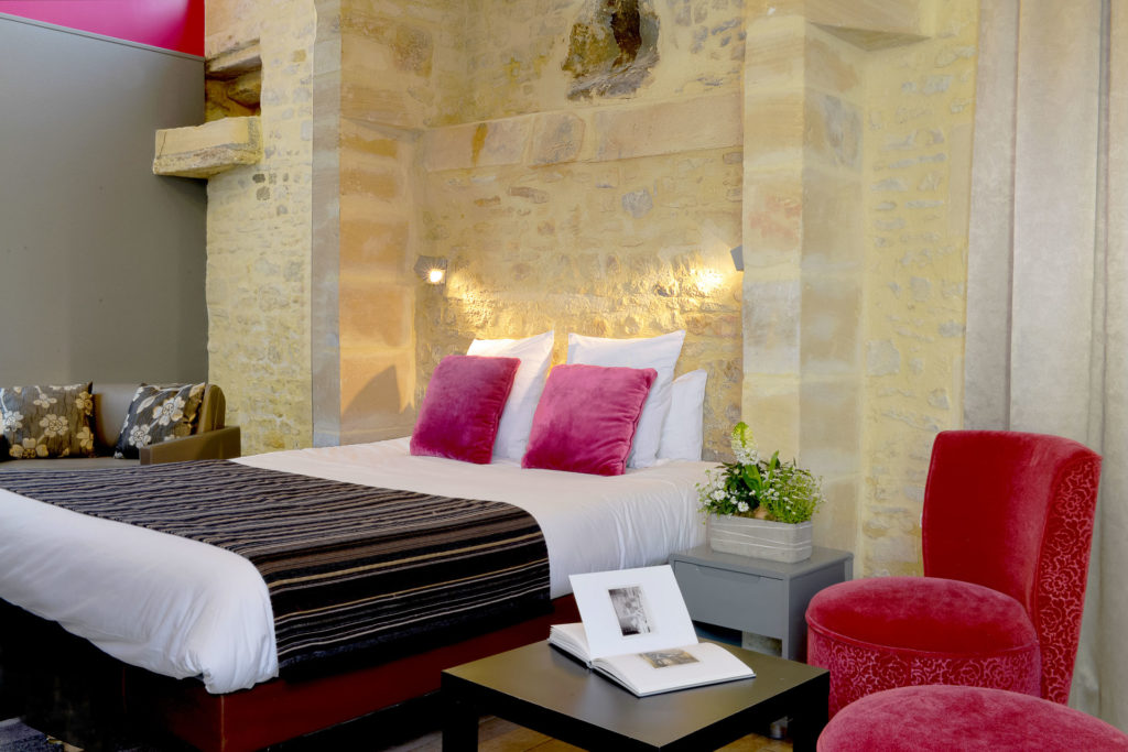 Room with bed, stone walls, pink cushions and trad furniture La Reine Mathilde Bayeux