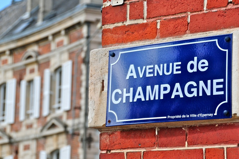 Avenue de champagne Blue sign in Epernay against red brick wall