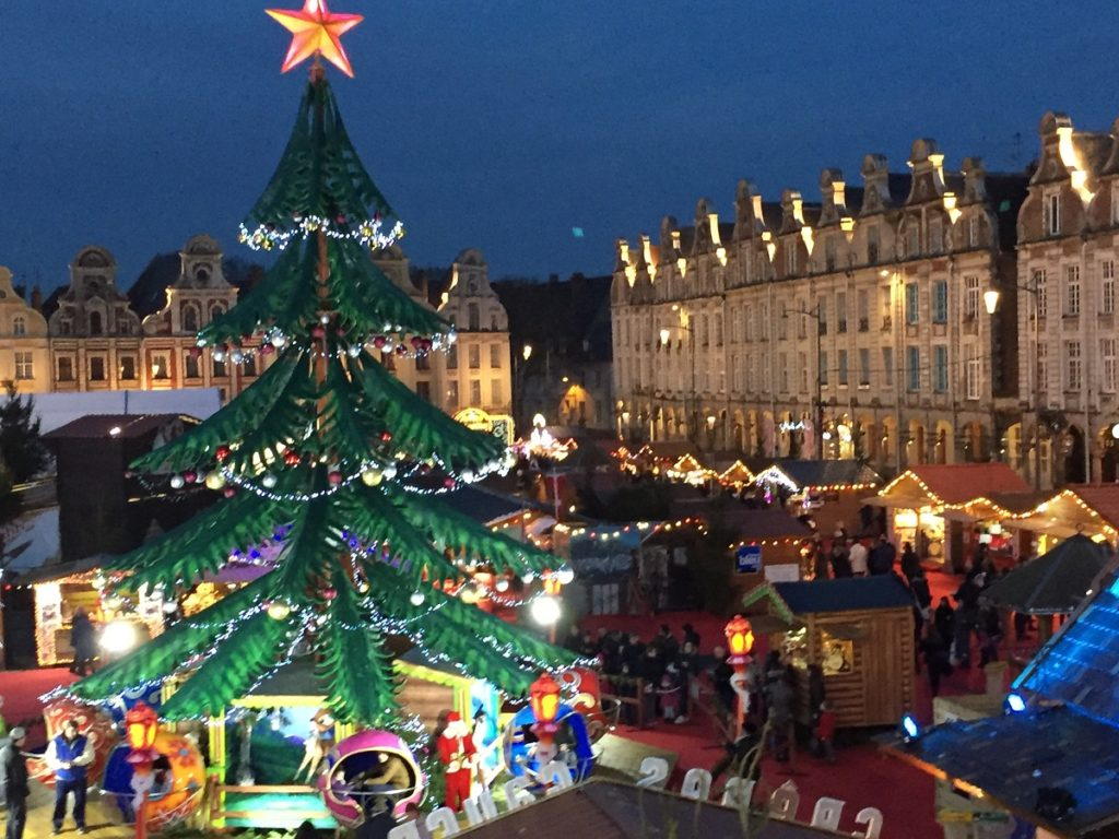 Arras christmas market with christmas tree in front and arras square behind at night