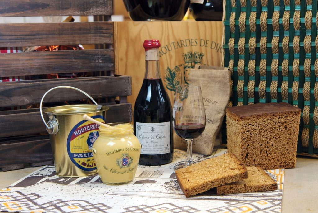 Setting of bottle of creme de cassis, pain d'epice, bread and mustard