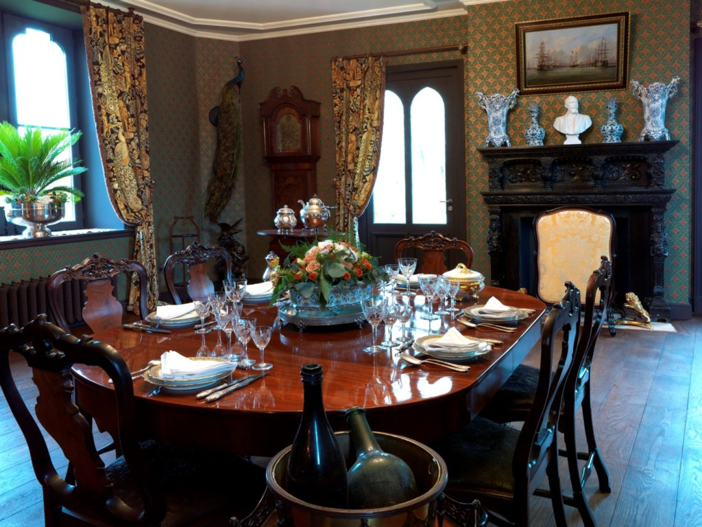 Victorian dark wood table adn chairs, blue carpet and heavy drapes at the Chateau Hardelot