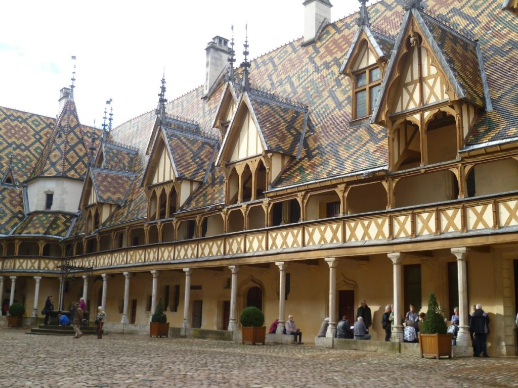 Hospice de Beaune building in inner courtyard with wooden gallery, magnificent tiled roof and pointed dormer windows