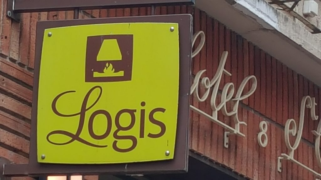 Logis hotel sign against red brick wall with Hotel words