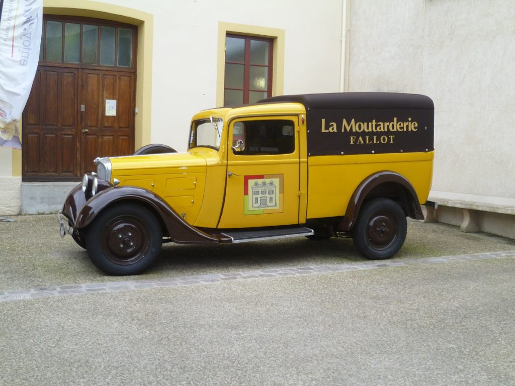 Yellow old fashioned Fallon Mustard van in courtyard