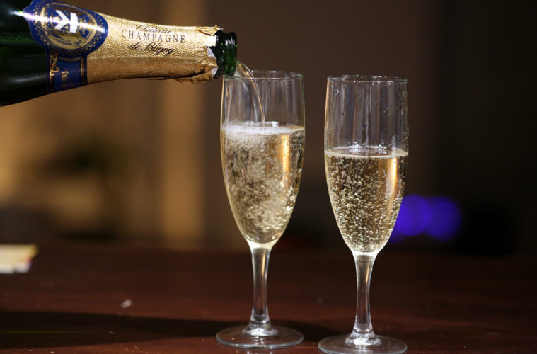 Champagne bottle pouring champagne into two glasses