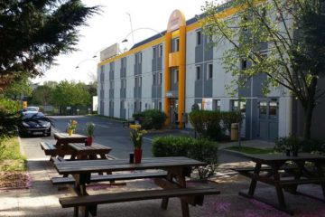 Look at premiere classe budget hotel from side with tables and chairs outside.