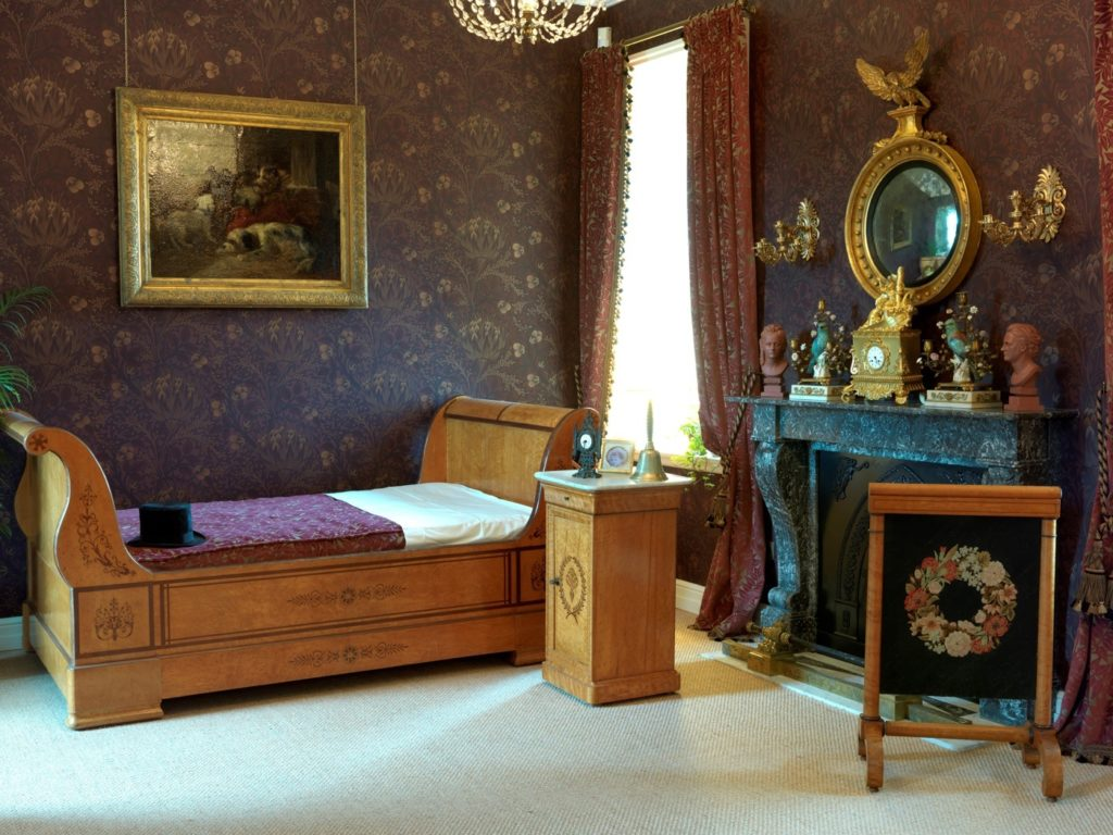 Day bed in dim lit bedroom with Victorian furniture and paintings at Hardelot Chateau