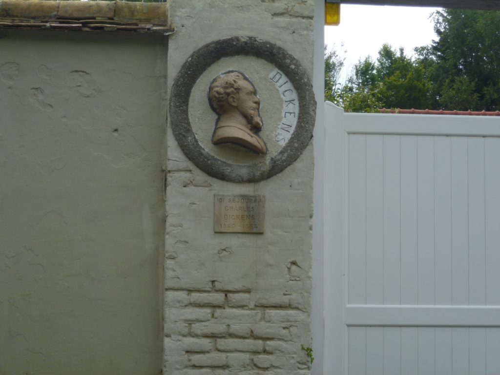 Plaque of head of Dickens and sign saying he stayed here