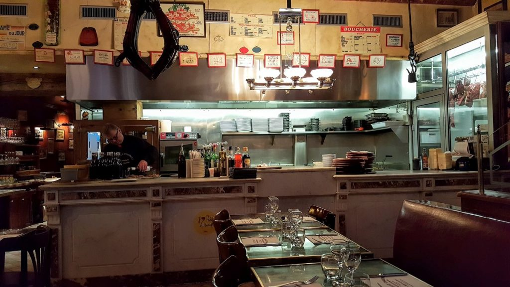Bouchon restaurant in Lyon with counter with meat, notices on the walls and tables in front