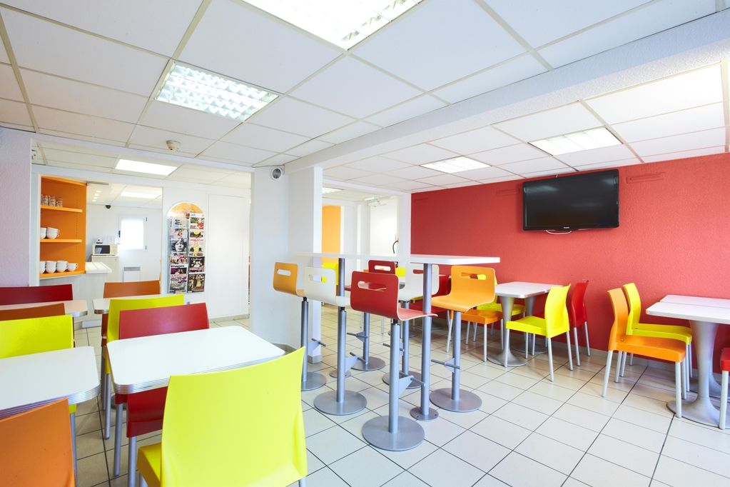 Premiere Classe 2-star hotel cafe with bright coloured chairs and walls