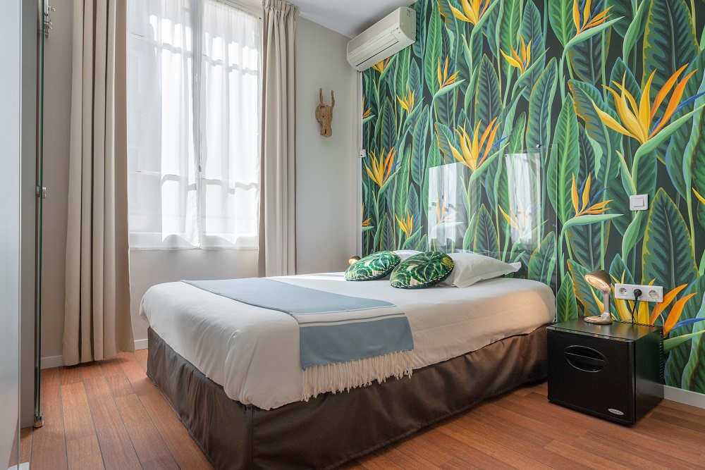 Hotel Cecil in Juan les Pins bedroom with green jungle stle wallpaper on one wall, large bed and large window