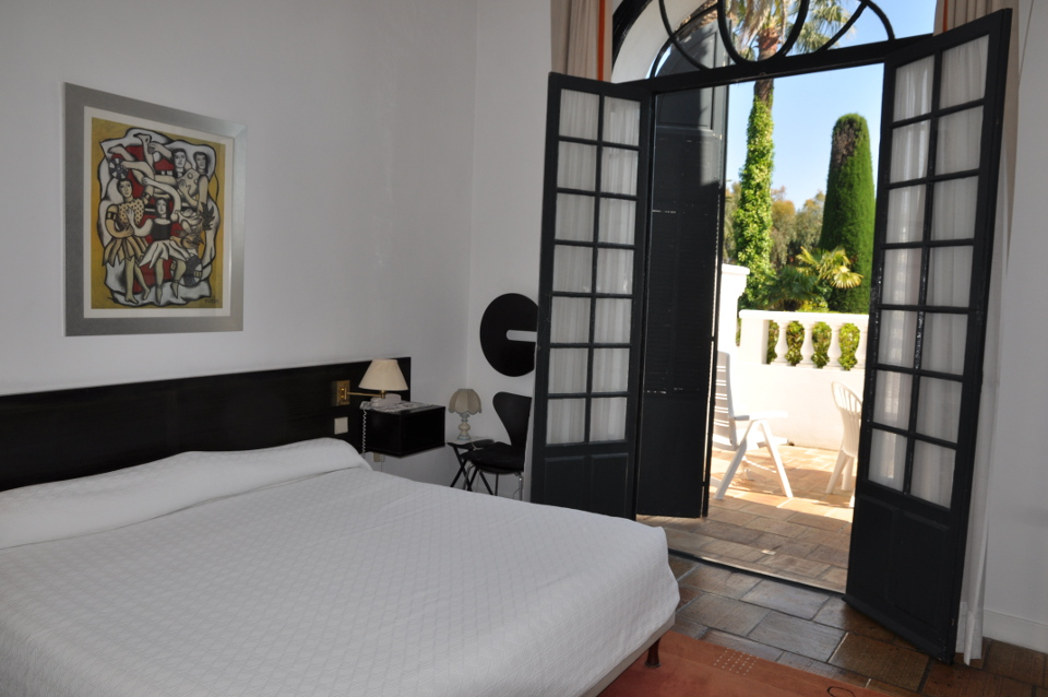 Hotel des mimosas bedroom with french doors opening onto a rterrace and large double bed