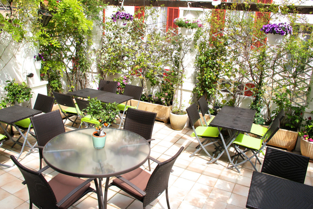 Eden Hotel terrace with tables chairs and greenery