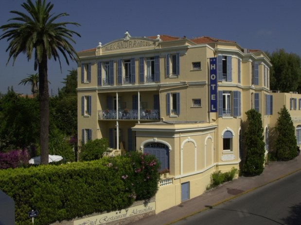 Hotel Alexandra in Juan les Pins exterior of elegant 19th century sand coloured hotel with garden and hedge in front